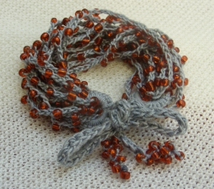Beaded crocheted grey and red bracelet